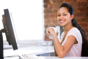Businesswoman in office drinking coffee and smiling